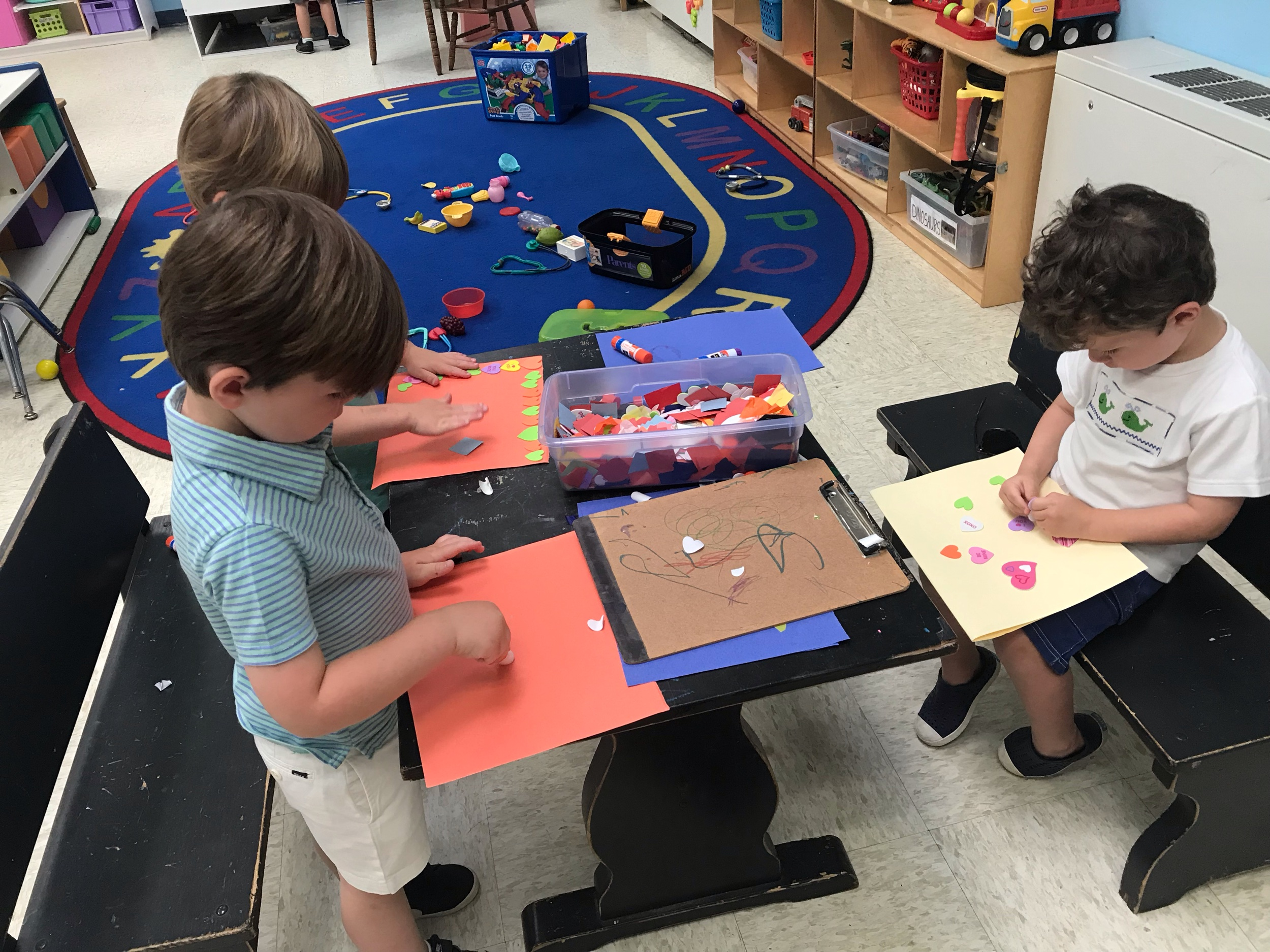 Creating a masterpiece with paper and glue sticks!