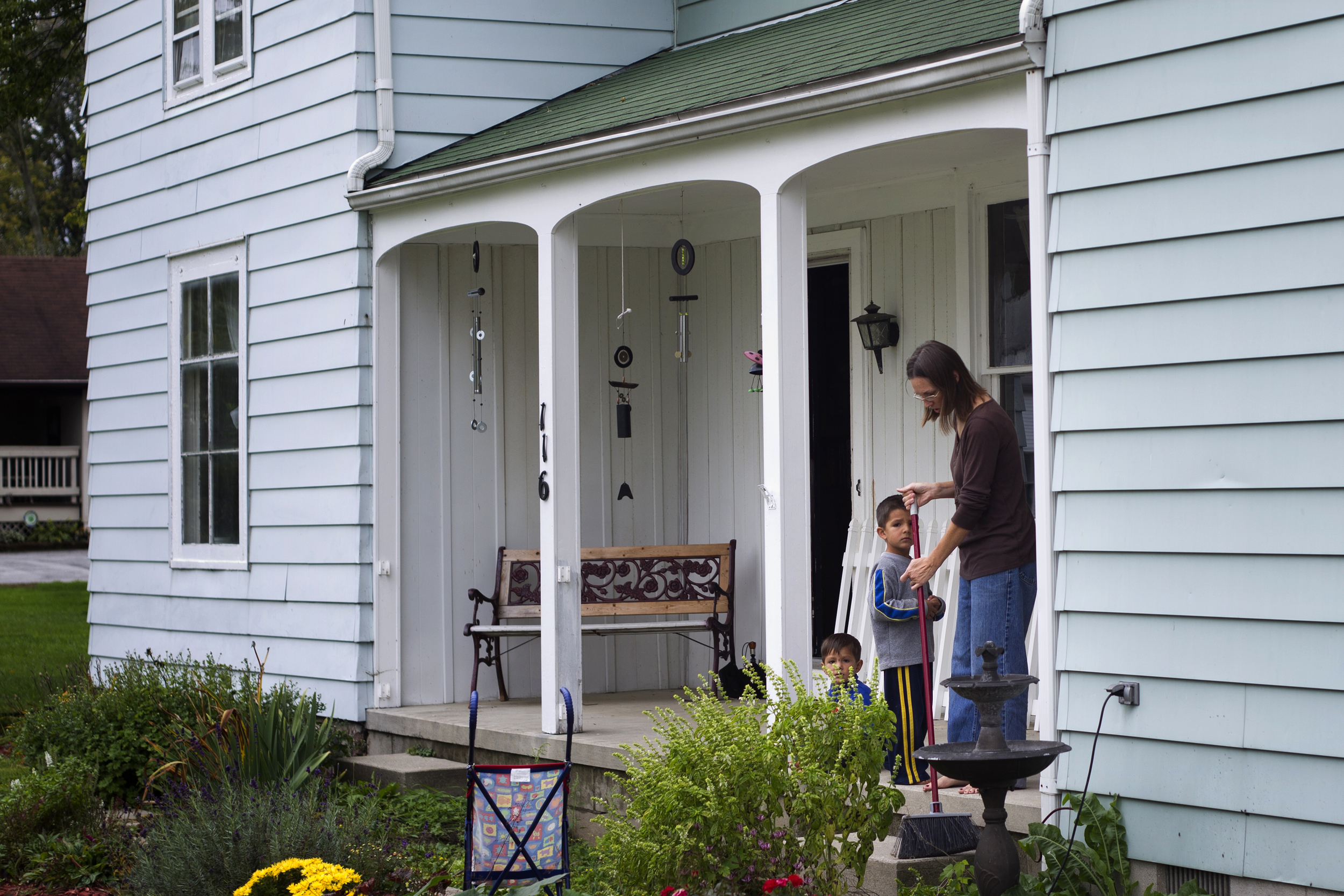 Rebecca Acosta, right, sweeps the front porch of her home in Pemberville as her children play in the yard. Though she said that she, herself, benefits from from some of the policies aimed at helping the poor, she was strongly against increasing taxes on the wealthy to help fund those policies.