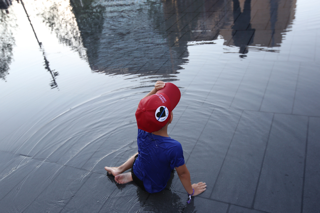 """Leo, 5, sports a, """"Make America Great Again"""" hat as he plays in the water at Public Square as his father Peter Trunzo of Cleveland keeps an eye out nearby on the third day of the Republican National Convention Wednesday, July 20, 2016, in downtown Cleveland. Among the thousands of people flocking to the attend the convention at the Quicken Loans Arena hundreds of people also turned out to protest and counter protest. As a rare Republican in Cleveland Mr. Trunzo said he'd come downtown to soak up the atmosphere. """"We're such a bastion for the other side that it's nice to come out and see all the Republicans,"""" he said."""