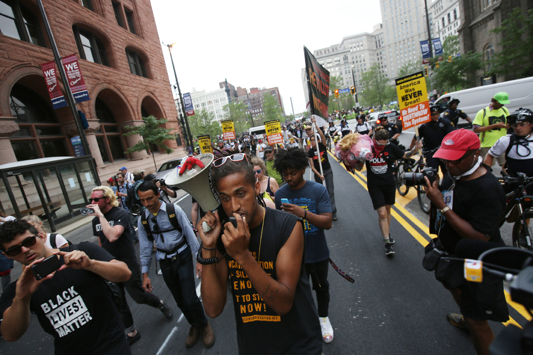Turner Farr of Cleveland, center, leads an impromptu march Thursday, July 21, 2016, calling for free speech and the release of several people with the Revolutionary Communist Party who were detained during a flag burning protest during third day of the Republican National Convention in Cleveland. Lawyers with the Cleveland branch of the NAACP and the Ohio chapter of the National Lawyers Guild had offered to represent the 17 people arrested. All but two were released Thursday.