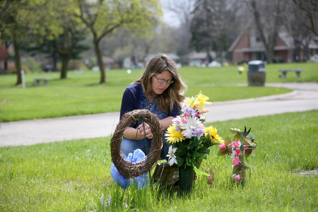 "Josianne Thomas kneels at the grave of her two eldest children Joscelyn and Johnny, who were 16 and 14 when they were murdered in the fall of 2015 in an attack by Joscelyn's boyfriend. Josianne survived being stabbed more than 12 times in the same attack. She visits the cemetery weekly, often with her two surviving children, now four-year-old twins Tiffany and Hailey. ""It feels like I should have a calling for something, some reason why I'm still here,"" she said."