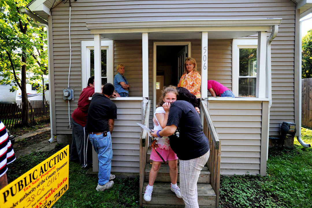 Jordan Cannon, 7, center, hugged her cousin's girlfriend, Misty Johnson, as the two stood on the steps of a home during a tax foreclosure open house in Jackson. Cannon's father, Rev. Gordon Cannon, far left, said he was looking into buying the home for his son, not pictured, after he graduated high school. This two bedroom, one bathroom ranch house was going up to auction with a minimum bidding price of $4,650. Minimum bids begin at the price of back taxes on a property. The low price can allow families to purchase homes who might have bee unable to do so otherwise.