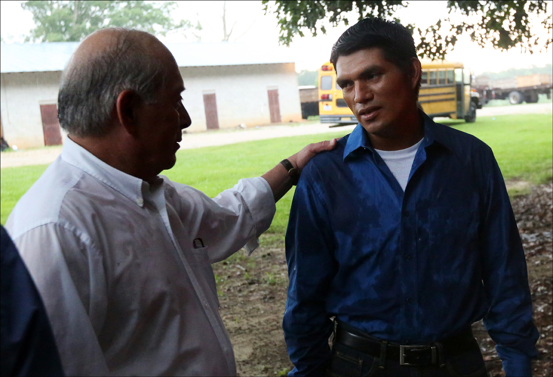 FLOC President Baldemar Velasquez, left, speaks with a migrant worker, who agreed to be photographed but declined to be named, outside the cinder block building where he lives. The union, which was founded in Ohio, has been expanding south. Many tobacco workers are undocumented immigrants and fear reprisal from their employers for union involvement.