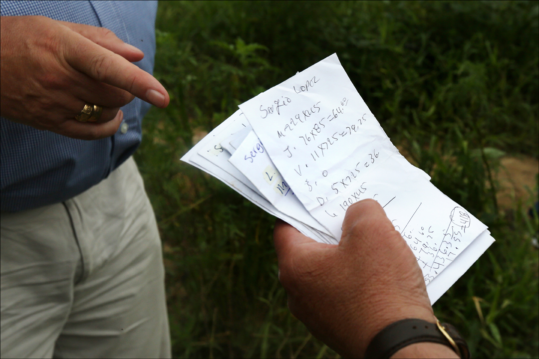 Handwritten payment slips, delivered to migrant workers, are inspected during a tour of migrant laborer camps Sunday, July 28, 2014, organized by the Farm Labor Organizing Committee, AFL-CIO (FLOC), outside Raleigh, North Carolina. British Members of Parliament Ian Lavery and James Sheridan toured two migrant camps with FLOC President Baldemar Velasquez.  Mr. Velasquez alleges the slips are a violation of North Carolina labor law. 