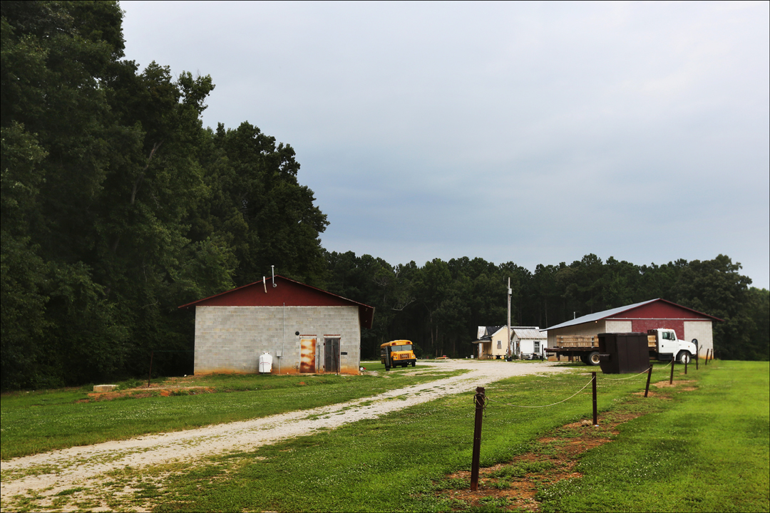 A migrant camp is tucked behind a line of trees, out of view of anyone driving along the nearby road. The Farm Labor Organizing Committee, AFL-CIO (FLOC) is working to unionize tobacco workers in North Carolina.