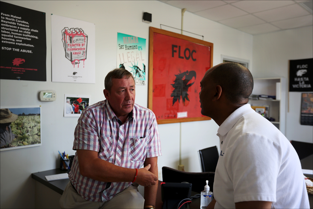 British Member of Parliament James Sheridan, left, speaks with AFL-CIO Executive Vice President Tefere Gebre share a word at the headquarters of the Farm Labor Organizing Committee, AFL-CIO (FLOC), near Dudley, North Carolina. U.S Congresswoman Marcy Kaptur (D-OH) was joined by British Members of Parliament Ian Lavery and James Sheridan for a tour of tobacco workers' homes and a tobacco field where worker's were suckering and topping plants as part of an effort by FLOC to garner political support for their campaign to unionize North Carolina's tobacco workers.