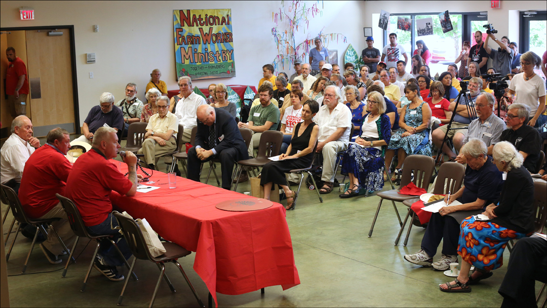 More than 100 FLOC members, supporters and allies gather Sunday, July 28, 2014, for a round table discussion with British Members of Parliament Ian Lavery, at table center, and James Sheridan, at table right, after their two-day-long tour of migrant laborer camps in between Dudley and Raleigh, North Carolina.