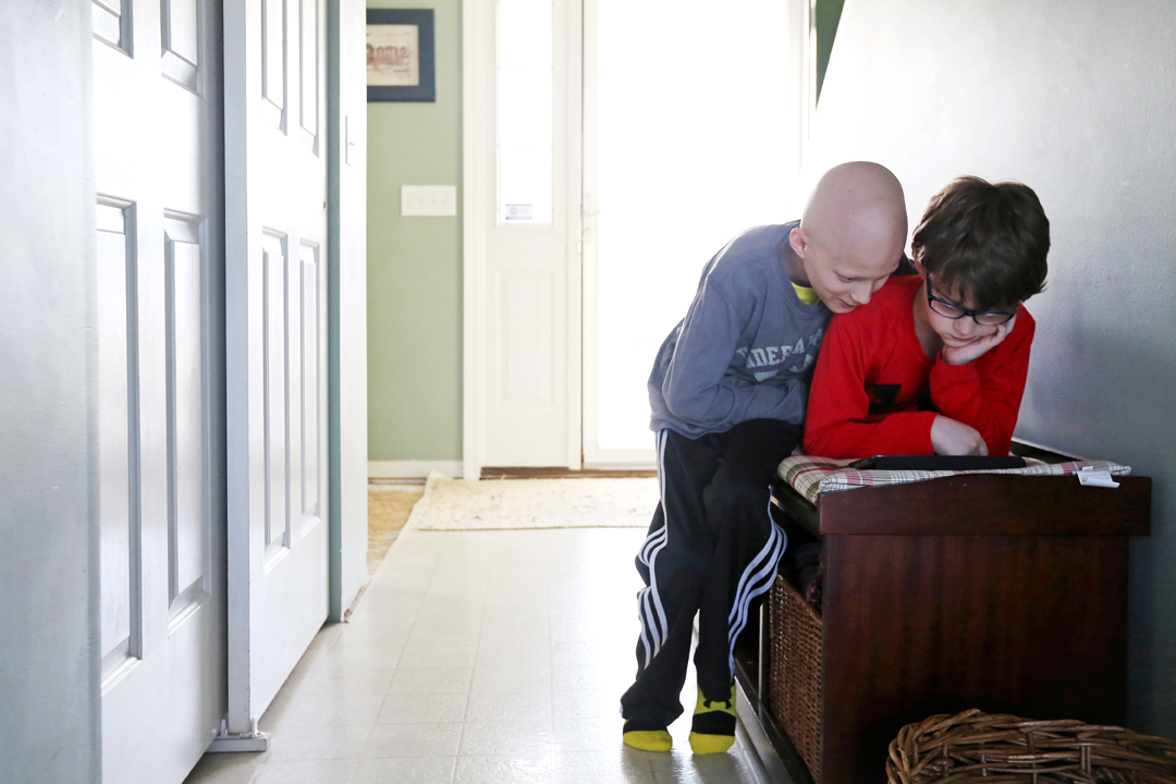 "Gavin Boggs, 11, left, helps his brother Zachary, 9, with his iPad game ""Clash of Clans"" at the family's home in Rossford. Gavin was diagnosed last year with a rare form of bone cancer called localized Ewing's Sarcoma. Since then he has undergone weeks of chemo treatment and surgery to replace the humerus bone in his right arm. The brothers have become closer during Gavin's illness; he was unable to leave the house or see many other children for months on end."