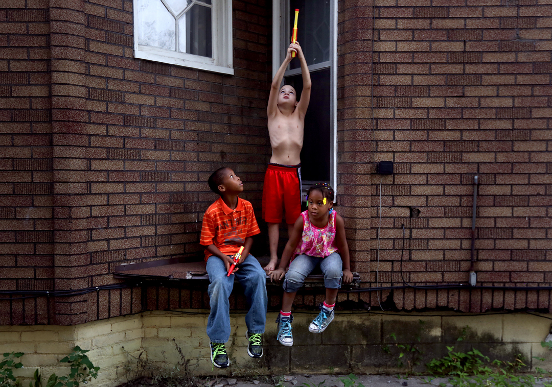 "Devin Whaley, 10, left, D.J. Ferrell, 9, center, and Zyaire Whaley, 6, play together on their block in South Toledo. The kids had forwent their squirt guns even though the City of Toledo had declared the tap water safe to drink earlier Monday, August 4, 2014. Toledo's water was declared unsafe for consumption in an emergency after officials detected heightened levels of a toxic algae byproduct in the water. Though the water was declared safe to drink, many local residents remain skeptical. D.J.'s mother, Krystalynn Ferrell, said she didn't trust the water just yet. ""I'm pregnant, so I'm not taking any chances,"" she said."