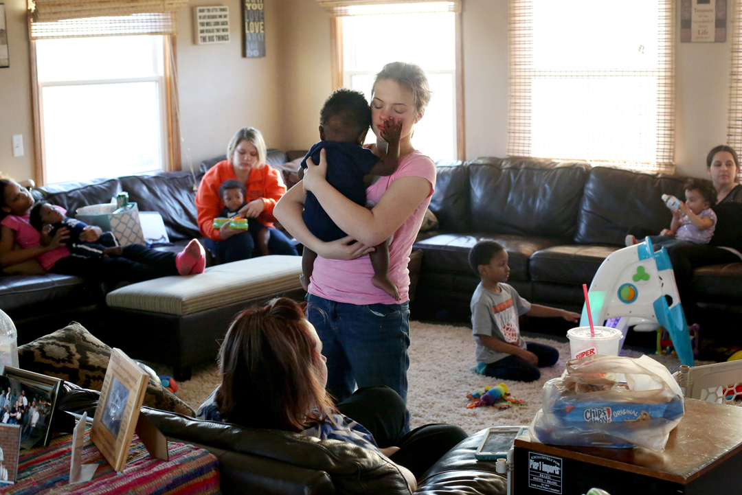 Raelyn Fenton Gogol, 12, holds her soon-to-be uncle Isaac, 1, who is blind, as he feels her face while their extended family visits together during a weekly dinner at the home of Kriste and Jeff Little in Walbridge. The Little's have been foster parents for more than 20 years and have adopted several of their foster children. In total, 10 of their kids live in the house right now, though Kriste says she doesn't differentiate between those whom she and Jeff have legally adopted and those who are staying with them as fosters. Kriste and Jeff are in the process of adopting Isaac and his two triplet brothers Elijah and Isaiah, each of whom have medical issues stemming from their premature birth and in utero drug exposure.