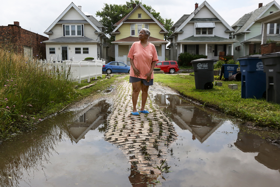 Norma Jean Williams, 72, stands near a flooded area of Norwood Court, an old brick road located just outside downtown Toledo. Ms. Williams has lived at a home located on Norwood Court since 1991 and has watched it crumble into severe disrepair. The court's six houses are nearly inaccessible via the road, which is deeply bowed and often flooded. Though the City of Toledo is responsible for the trash, sewer and ploughing of the road, it is technically private and therefore remains in severe disrepair. The City of Toledo is strapped for cash, spending only $20 million a year on the $1.3 billion it would need to repair the roads.