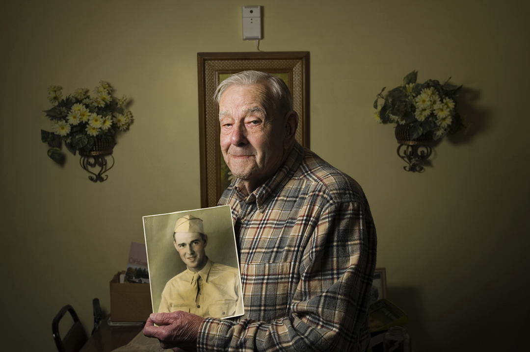 """Ival Hendrick, 93, holds a photograph of himself taken a few months before the attack on Pearl Harbor in 1941. Hendrick was stationed near the harbor when the Japanese attacked. The truck he caught on the way to the harbor got stuck in the road, leaving him and the men in it open targets for the Japanese who flew overhead. From his position he could see the ships under heavy fire.  """"I could see the boys in the burning water,"""" Hendrick said. """"Dec. 7 we didn't have no ammunition, we didn't have no guns. The only thing I had was a 1903 Springfield riffle."""""""