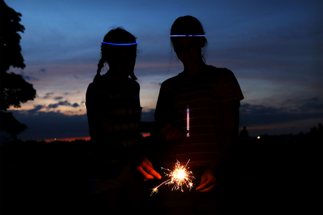 Maddie O'Dell, 13, left, and Sophie Twigg, 13, light their sparklers before the start of this year's fireworks display Monday, July 3, 2017, at Fort Meigs in Perrysburg. Thousands of area residents turned out on both sides of the Maumee River to watch the show, which included carnival rides and food at Fort Megs. The third of July is Maddie's birthday.