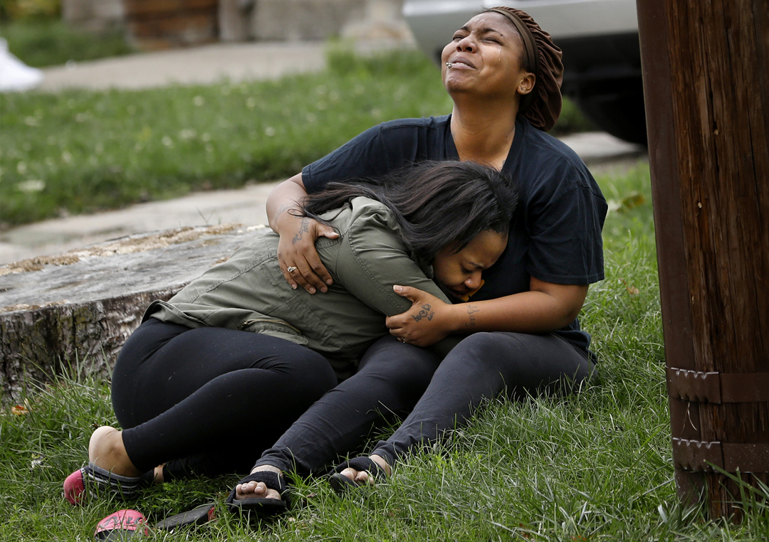 """That's my baby,"" a woman sobs, left, as another woman cries out, ""That's my brother,"" while holding one another in the front yard as Toledo police investigate a shooting Tuesday, October 10, 2017, at 729 Brighton Ave. in South Toledo. Toledo police spokesman Sgt. Kevan Toney said an 18-year-old man and 18-year-old woman had been pronounced dead after the shooting. Police later identified the victims as Gregory Stone and Deiyana Porter, who were shot while in a car parked behind the house."