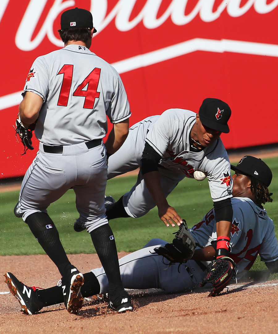 Indianapolis' Eric Wood (14) Christopher Bostick, center and Gift Ngoepe, right, can't make the catch off a Mud Hens hit in the bottom of the first inning during the Saturday, April 15, 2017, baseball match up at Fifth Third Field in downtown Toledo.