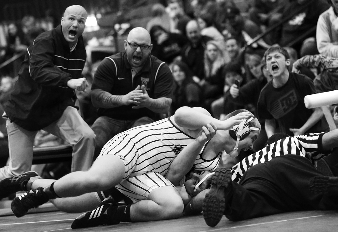 Napoleon's Andrew Pettit, center, his coaches and supporters cheer together as Pettit pins Maumee's Brandon Phillips during the 220 pound weight class match at the Saturday, February 7, 2015, Northern Lakes League Championship meet at Springfield high school.
