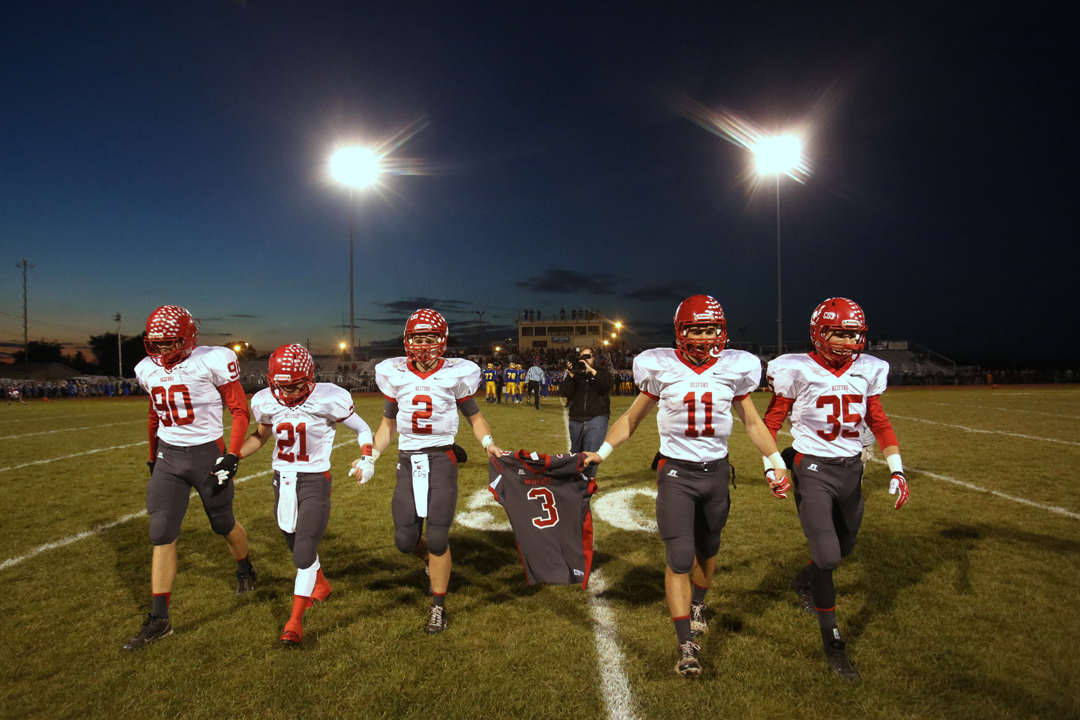 Bedford's senior Jeremy Harris (90) Lucas Mayo (21) Boss Brad (2) Alec Hullibarger (11) and Jack Maison (35) carry their teammate Colton Durbin's number three jersey off the field before the start of the Friday, Oct. 25, 2013, match up between Monroe Jefferson and Bedford. Bedford senior Colton Durbin was taken off life support Thursday after being injured in a car accident Wednesday. In addition to a moment of silence held before the beginning of the game, Colton's family and friends wore buttons, face painting and held his number aloft in his honor.
