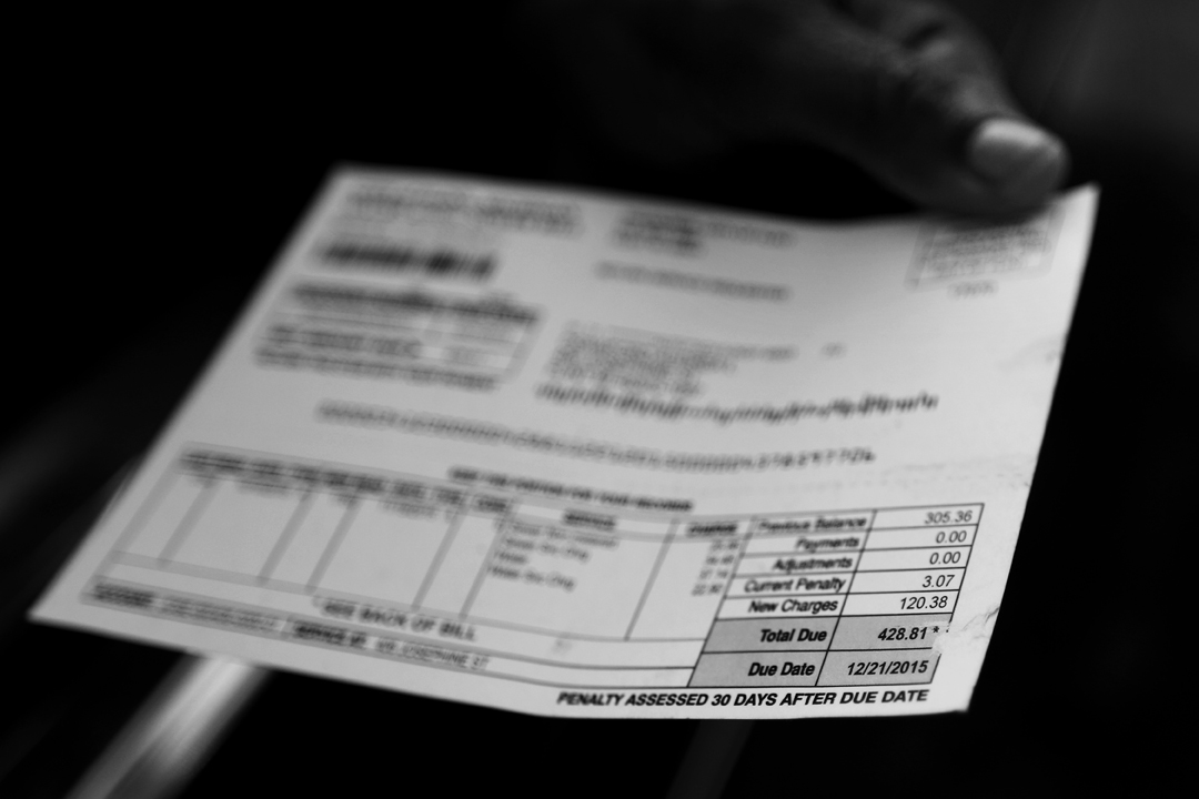 Flint resident Audrea Crawford holds out her city water bill after stopping at a distribution site to pick up a case of bottled water Wednesday, January 20, 2016, in Flint, Michigan. Ms. Crawford says her bill of $428.81, which was due on December 21, 2015, is far too high for water that cannot actually be used.