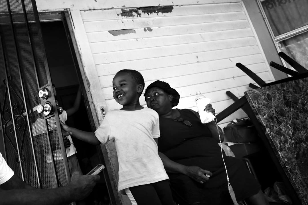 Jeremiah Slaughter, 5, left, plays on the front porch of his grandmother's house Wednesday, August 16, 2017, in East Cleveland. His grandmother Brenda Slaughter, right, said her family was moving out of their rental property after nine years because their landlord hadn't complied with ordered lead abatement. Because lead is present in virtually all homes built before 1978, when lead in paint was outlawed, many low-income families end up moving from one rental with lead hazards to another.