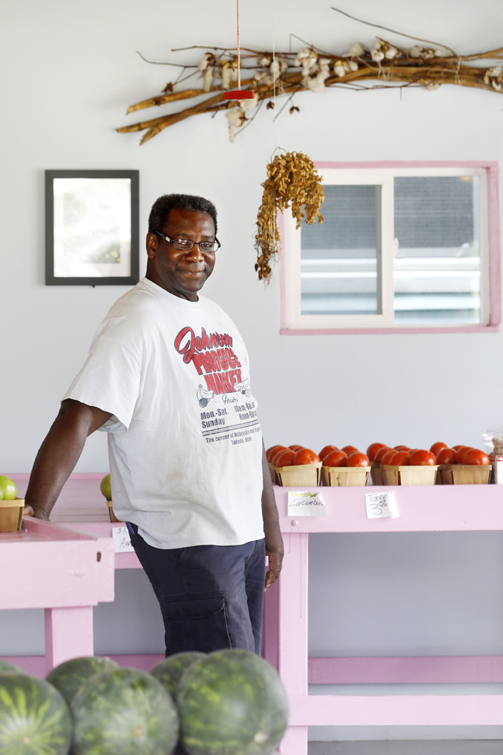 """""""I keep them to remind me of where we come from,"""" David D. Johnson said of the dried cotton and peanut plant he hangs in his produce store in Toledo. Mr. Johnson is the owner of Johnson Produce Market, which is located in a neighborhood whose residents have few options for fresh, affordable produce. He grows a large portion of what he sells, both at a greenhouse around the corner from his store and on a five acre farm outside Toledo."""