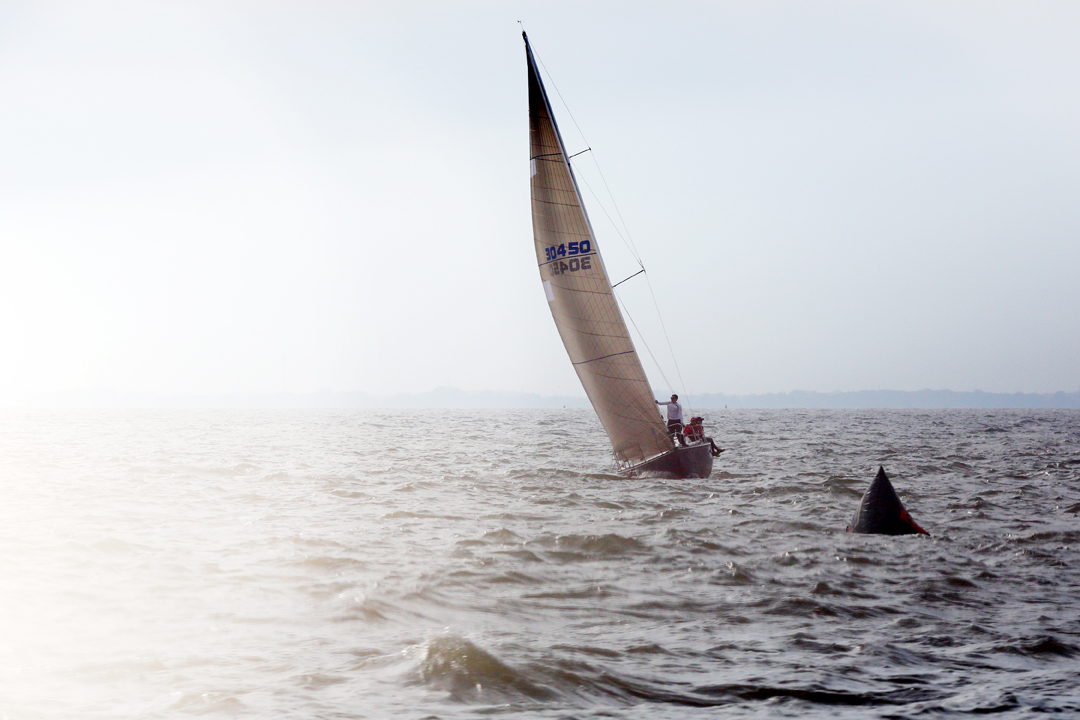 The sun pushes through the clouds as the Maverick, owned by Mark Keesey, heads toward the start line with the JAM C class at the President's Trophy race Friday, June 8, 2018, in Lake Erie north of Toledo. Sailboats in three races, the Mills Trophy Course, the Governor's Cup Course, and the President's Trophy Course, began at the same place and will end at Put-in-Bay in the Erie Islands.