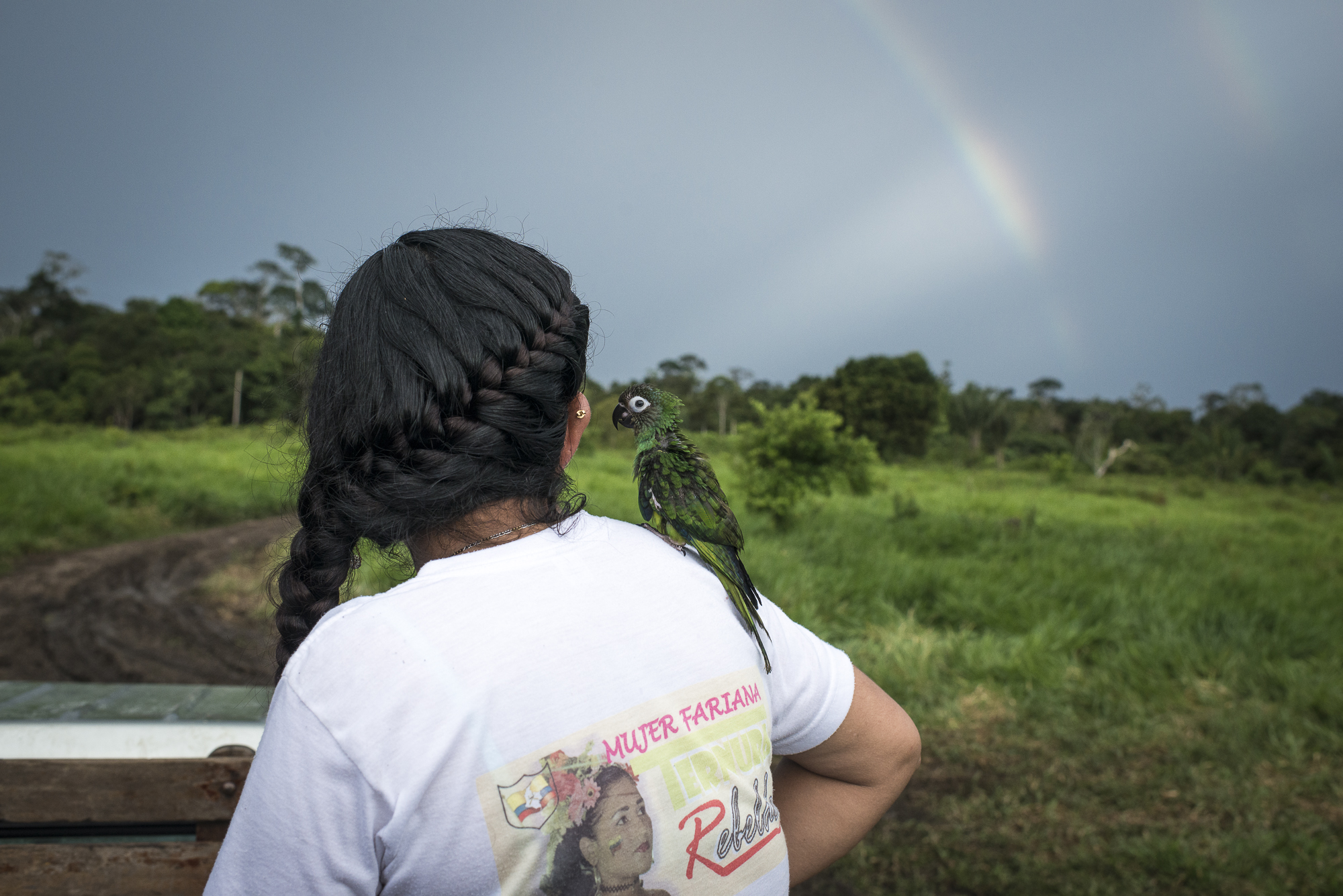 "June 2016, South Caquetá. Fernanda and Paquita, her baby parrot, are looking at a double rainbow at the end of a day. On her t-shirt is writing ""Mujer Fariana"", woman of the FARC culture.Criticized by the past for the lack of space given to female and LGBTI rights, the FARC guerrilla promoted in contrast a gender dimension into the first peace deal signed on September 26, 2016. But on October 2, 50,22% of the referendum voters rejected the agreement. A new peace deal has been negotiated and signed on November 24, with almost all the gender references removed according to the evangelical churches request, which were among the most powerful No promoters."
