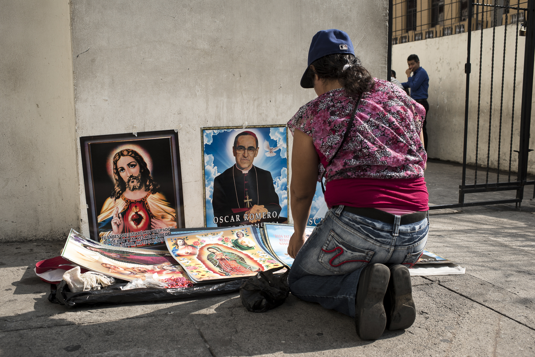 A Sunday morning at the time of the mass and near the Metropolitan Cathedral of the Holy Savior, a woman is selling some poster of the Christ and Monsignor Romero,archbishop of San Salvador taht was killed by the military and the beginning of the 1980. He still stays a popular and loved figure of the contemporary Salvador.