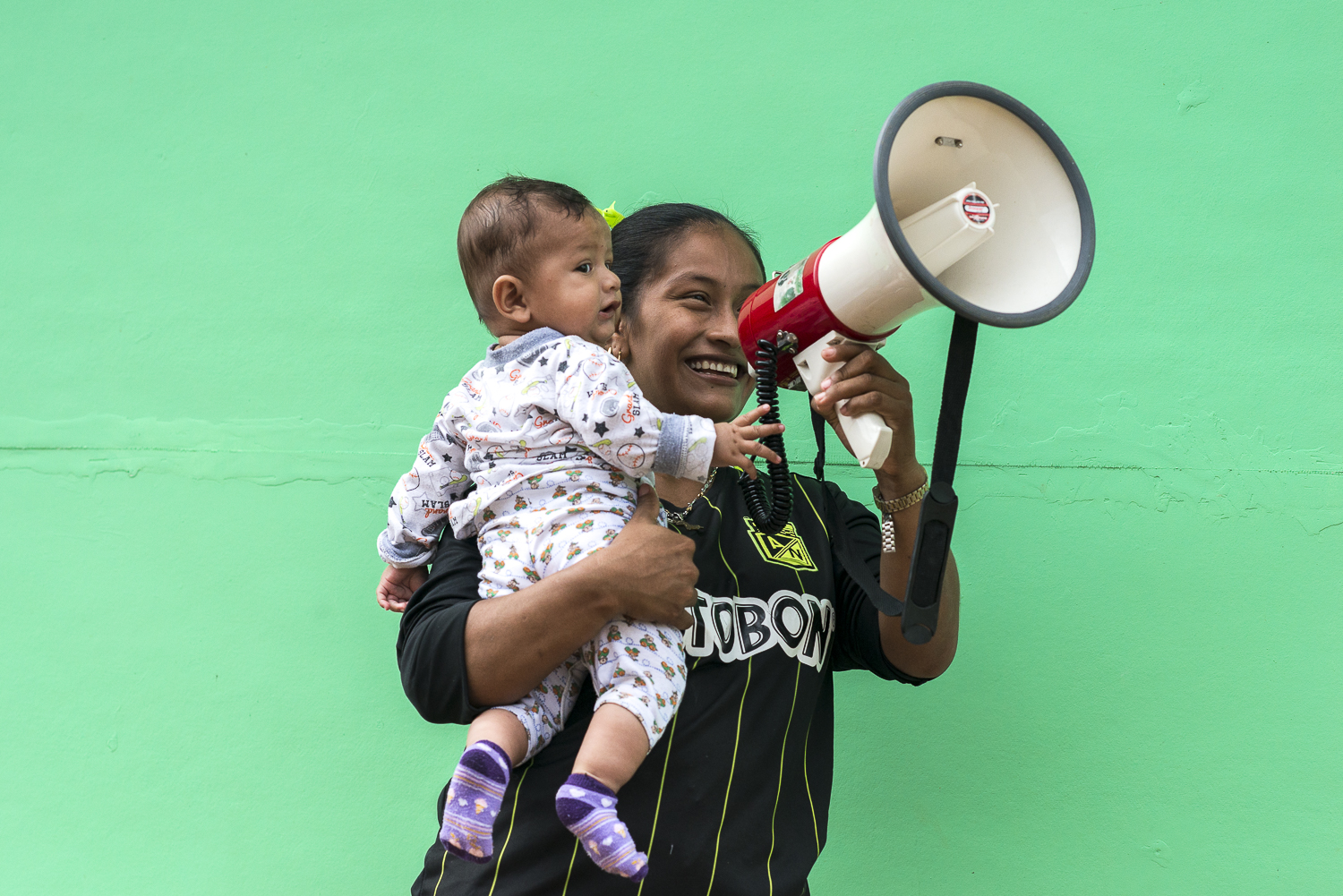 Daisy with her baby Jhorner, is posing with a megaphone. Once all the weapons hand over, the FARC guerrrilleros explains dedicate themself to the political and civil fdemocratic fight.