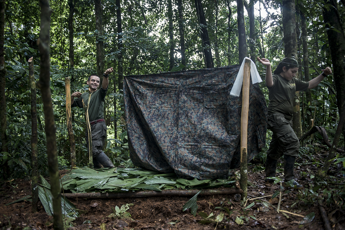 "The two guerrilleros are put up the ""caleta"": In the camp, every guerrillero settles into their own place under a camouflage tarp that protects them from the rain. They name it their ""home"". It prevents detection by the airplanes. In war times, their main fear was to be bombed by night. (October 14, 2015, North Caquetá)"