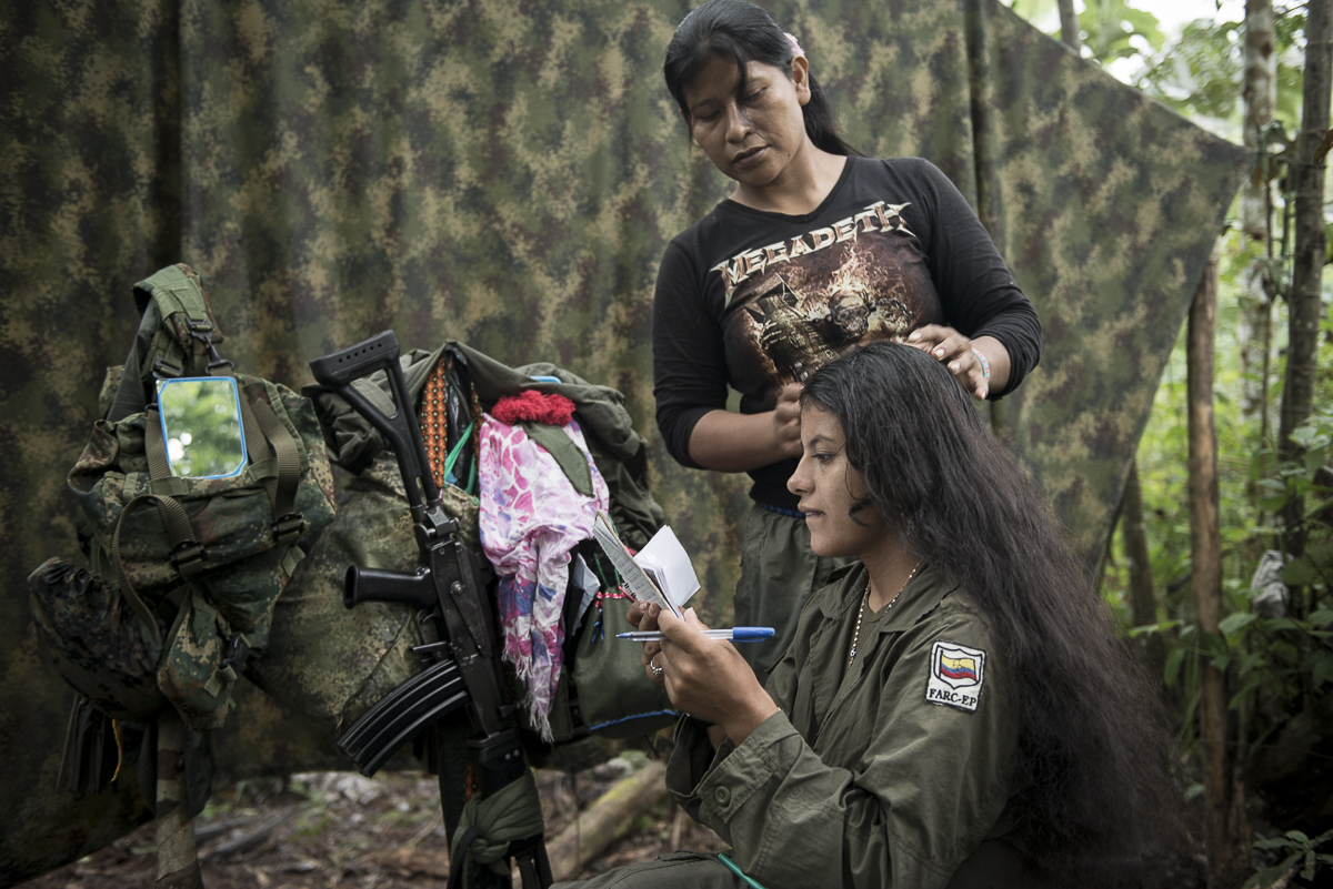 A guerrillera reviews the encoding of the messages she will send by radio to other groups or to the command, Her comrade begins to plait her hair. (May 11, 2015. South Caquetá)