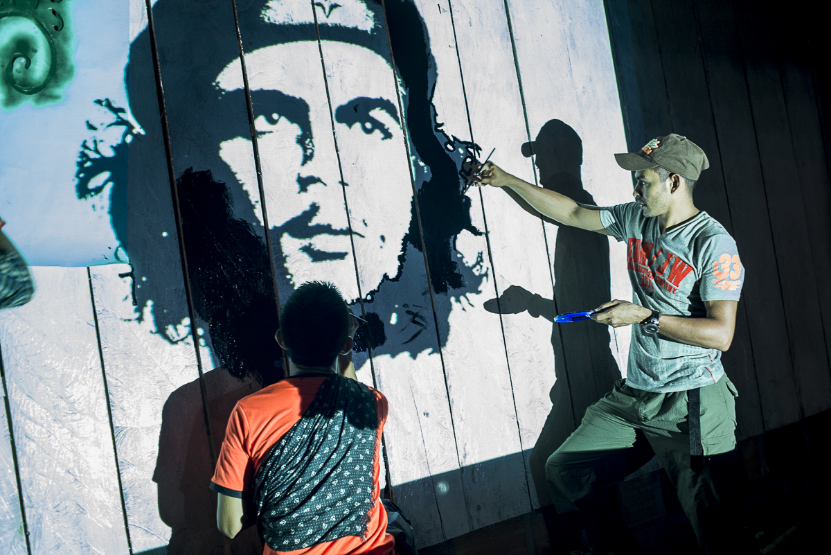 Two days before the meeting between the peace FARC delegation and the civil population, a local inhabitant and a guerrillero are painting the Che Guevara face, helping them with a video projector. (January 23, 2016, Putumayo)
