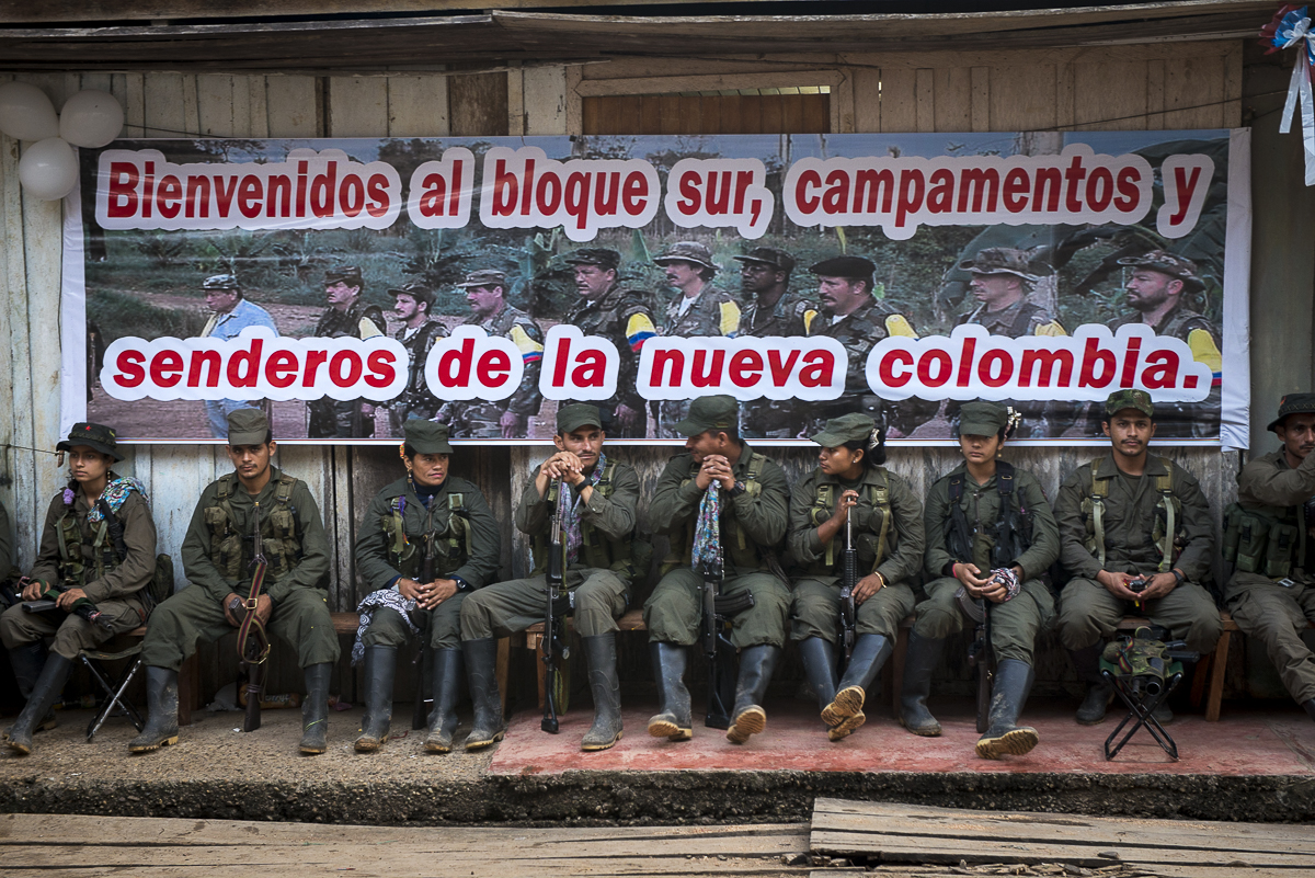"The guerrilleros are waiting to be assigned at a place during the public meeting between peace FARC delegation and civil population. The banner says: ""Welcome to the southern Block, the camps and the pathways to a new Colombia"". All the fronts and the columns are represented in the event. (January 25, 2016, Putumayo)"