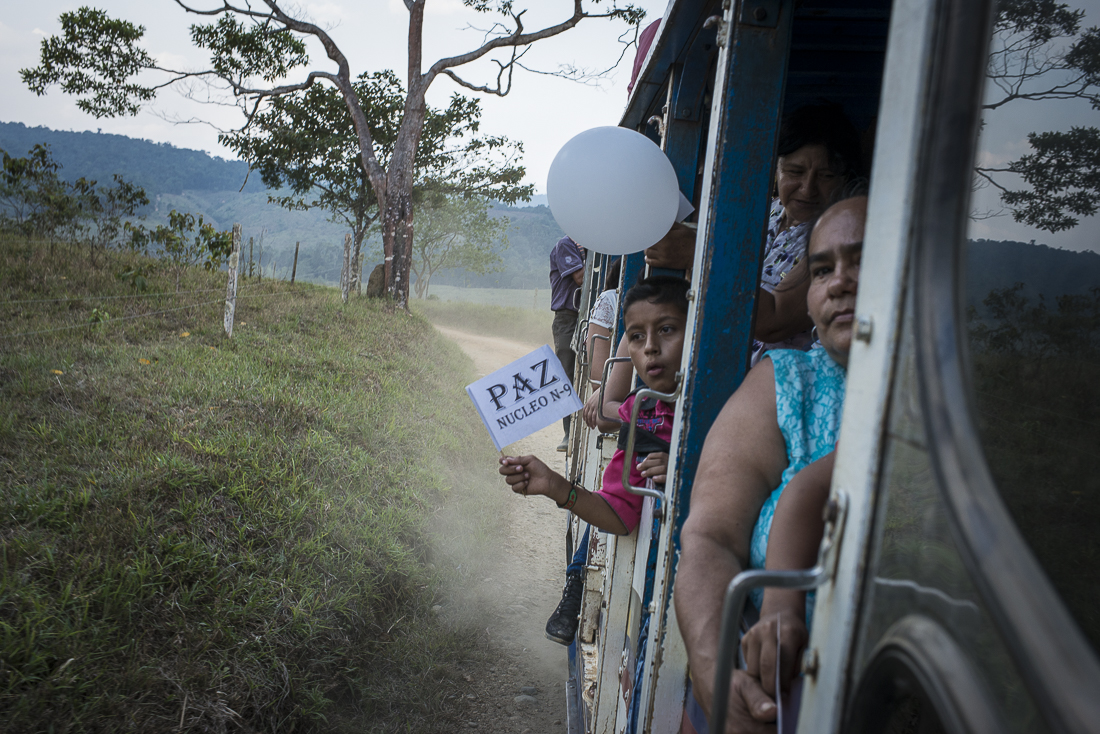 """A child waves a white flag with the writing """"Peace"""" on it. With his family, he comes back from a """"peace pedagogical"""" meeting where peasant organizations presented and explained the peace talks between the FARC guerrilla and the Colombian government at Cuba. (February 6, 2016. North Caquetá)"""