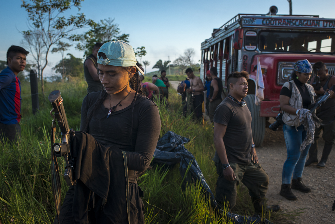 The caravan arrived near Campo Hermoso, where the guerrilleros takes another bus to travel on the paved road. A guerrillera is cleaning her weapon after the one-day trip on the chiva. (December 9, 2016, Caqueta)