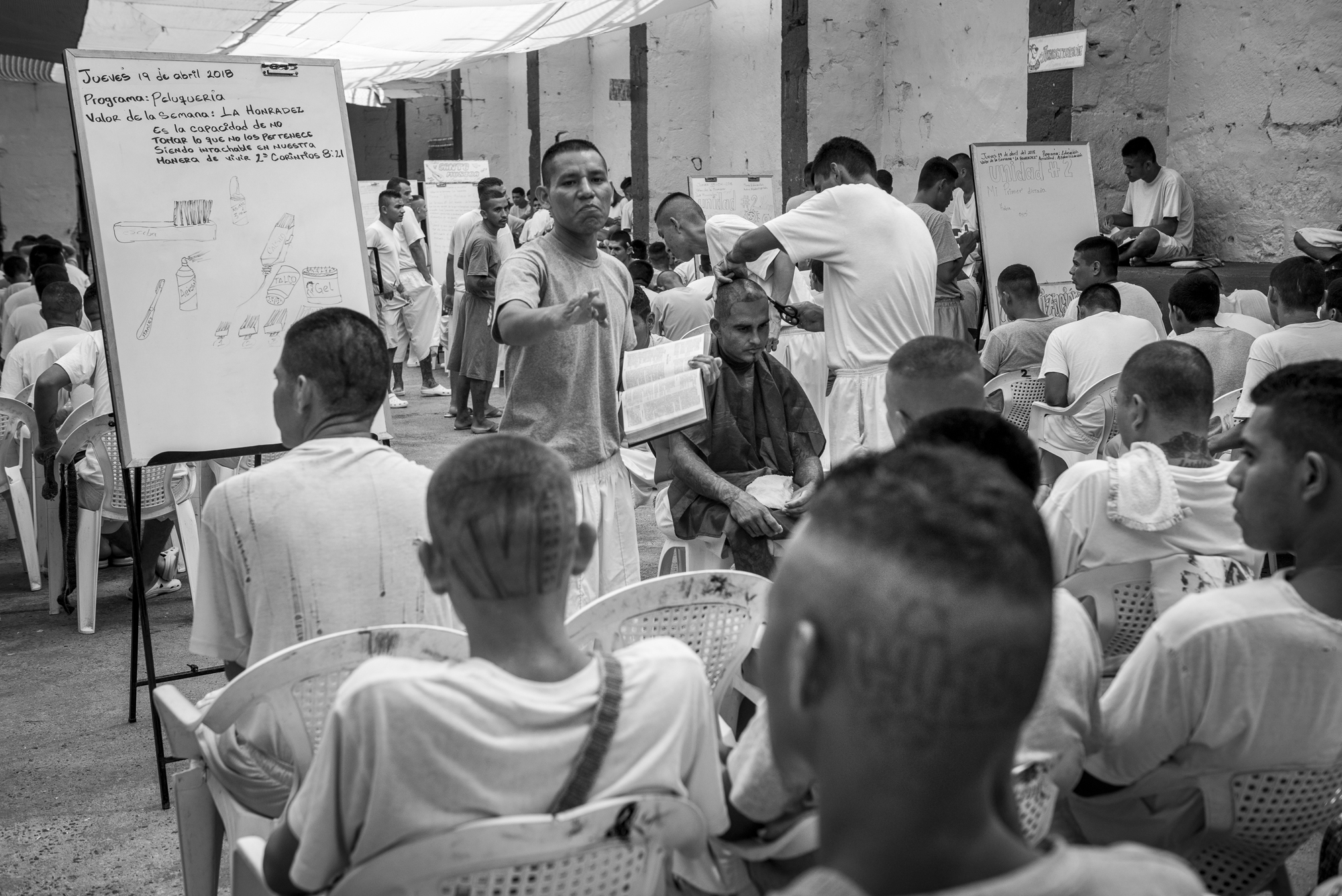 "A group of prisoners is listening the class an inmate is giving about haircut. A verse of the Bible is recalled on the whiteboard. Inside every yard, the inmates are participating to a class where they can learn a practical training (about bakery, serigraphy, carpentry, etc.), a religious education or an alphabetization class. Since almost two years, the government of El Salvador started a program of reinsertion inside the prisons, named ""Yo Cambio"", ""I Change"". In La Gotera jail, the director mixed the program with religious instructions."