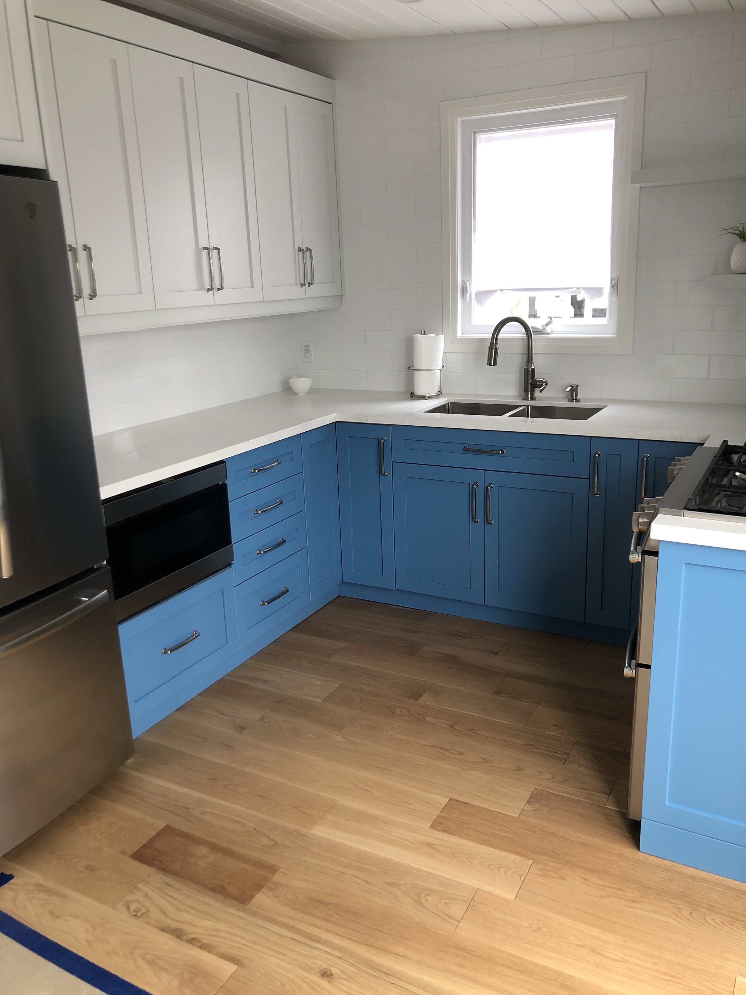 Dual Colour cabinetry with quartz counter, under mount sink, and new hardwood flooring.