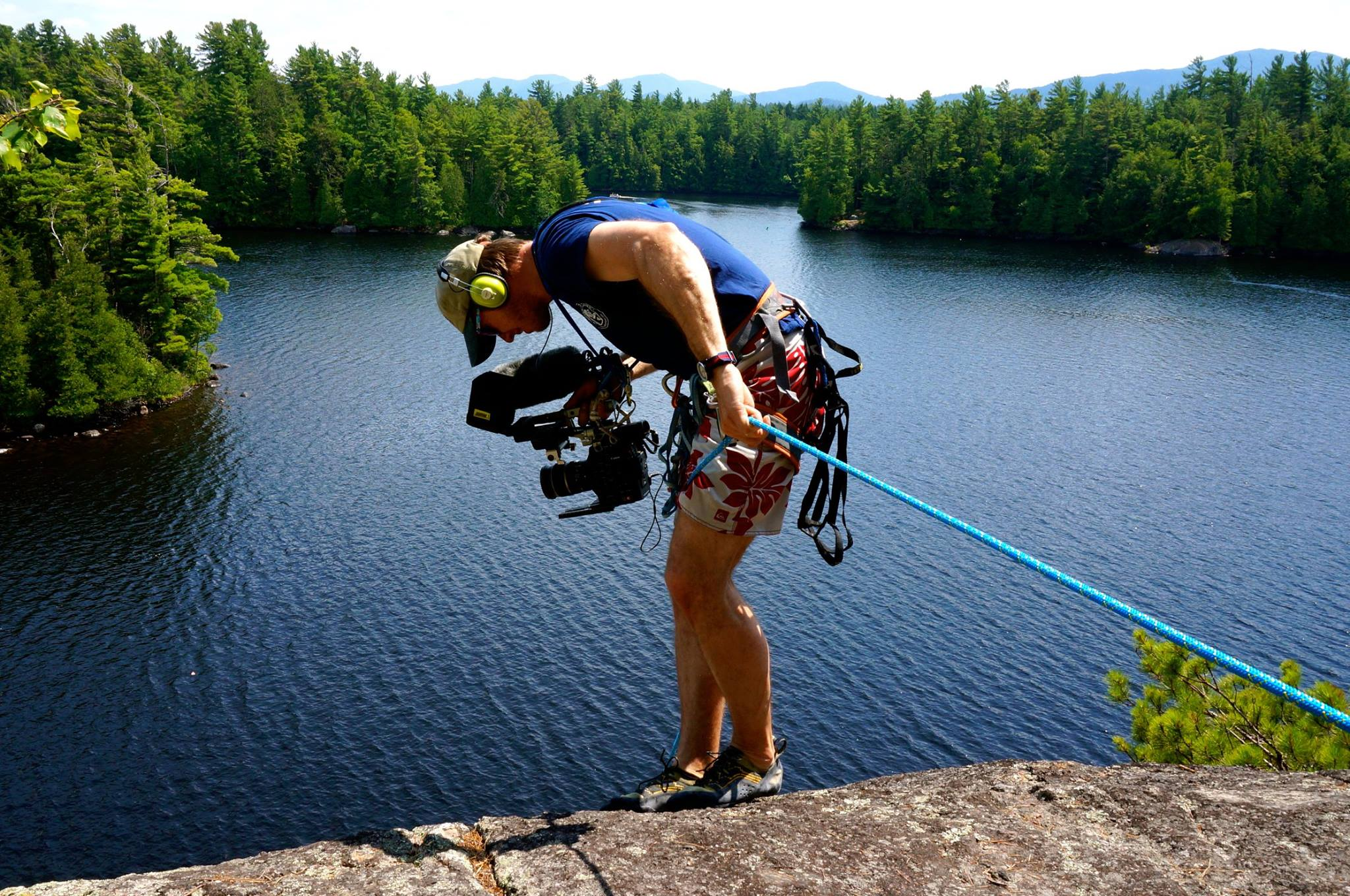 Rufus Lusk hanging off a cliff to capture a camper rock climbing over a lake in the Adirondacks