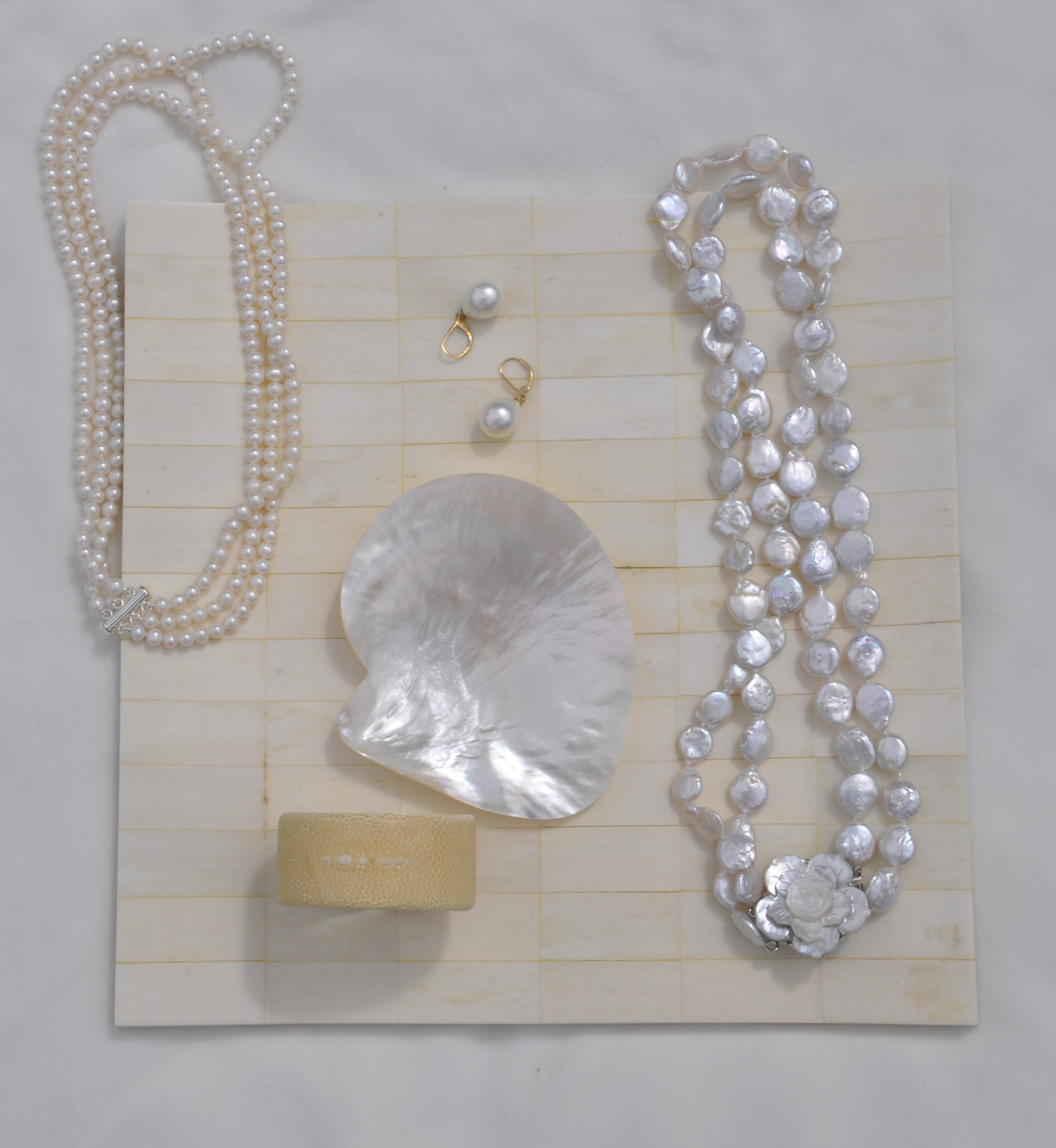 TOP LEFT: 3 strands round white freshwater pearls; CENTER: pearl drop earrings; RIGHT: 2 strand potato freshwater pearls w/ shell clasp; BOTTOM: cream shagreen petit cuff bracelet
