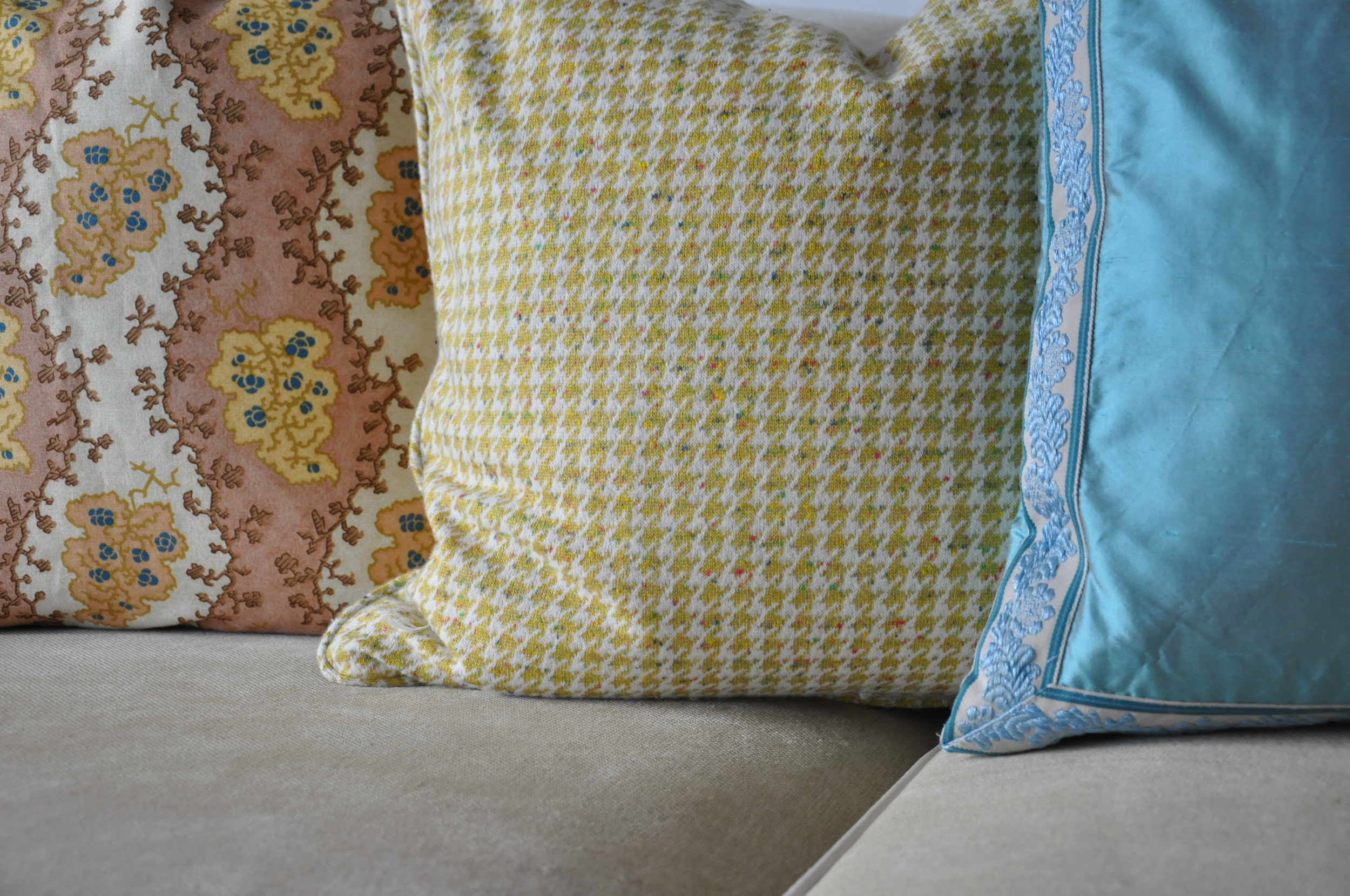 I love the bright color combination of a very English fabric, a yellow cashmere wool houndstooth, and a vibrant turquoise silk pillow. Sure to brighten in room!