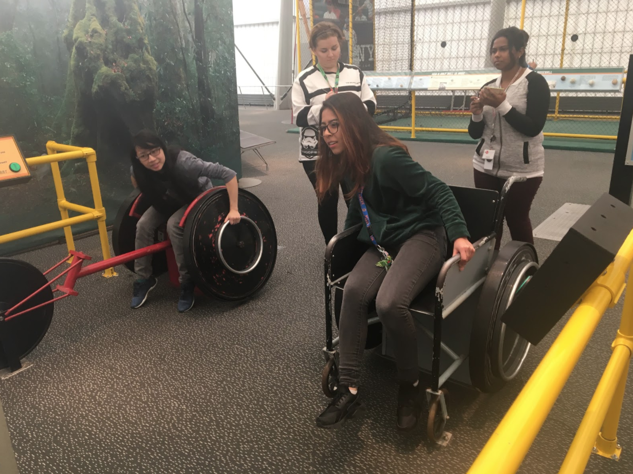 Samantha (left) and Leah (right) show off their brawn and their brains racing and talking about aerodynamics and speed while Yuliya (left) and Kumari (right) take note of the engaging aspects of this exhibit.