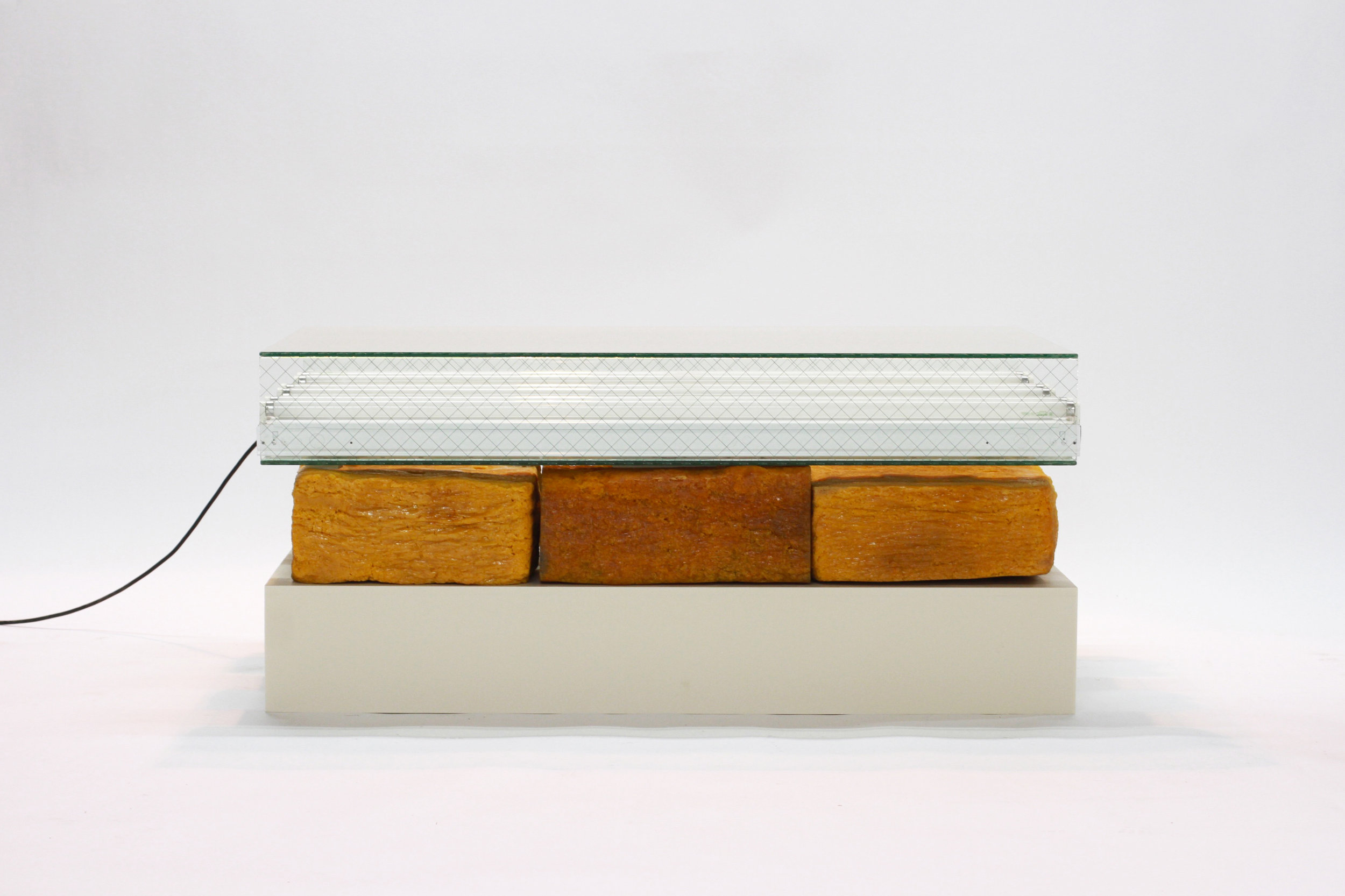 Lamp: Three tiered assemblage of a Corian platform, rubber bales, and fluorescent fixtures arrayed in wire glass