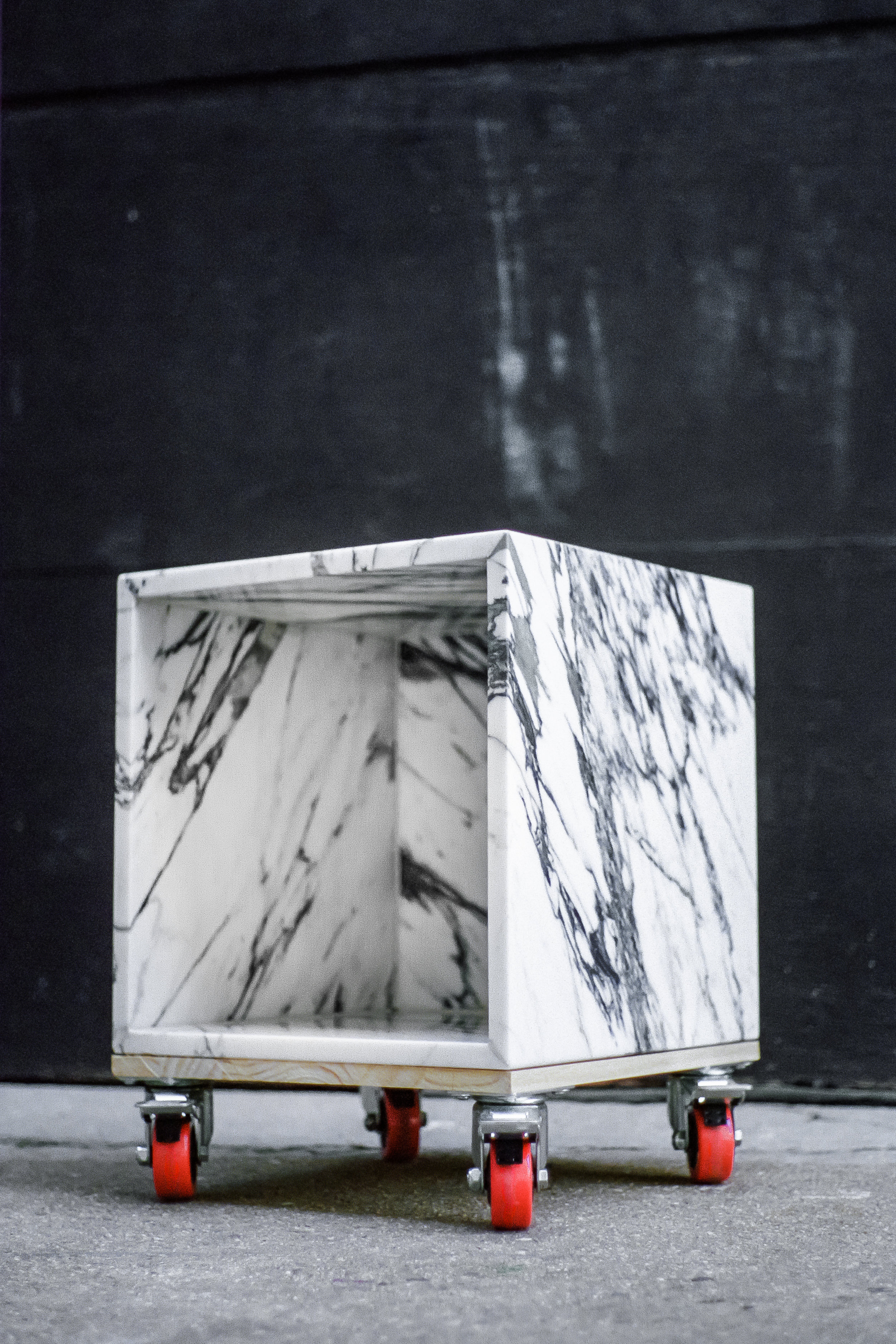 """Dozie Kanu. """"Marble Cube TABLE"""" (2016). marble STONE, READYMADE casters. 16 x 16 x 20 inches. Courtesy the artist. Photo: Joshua Aronson."""