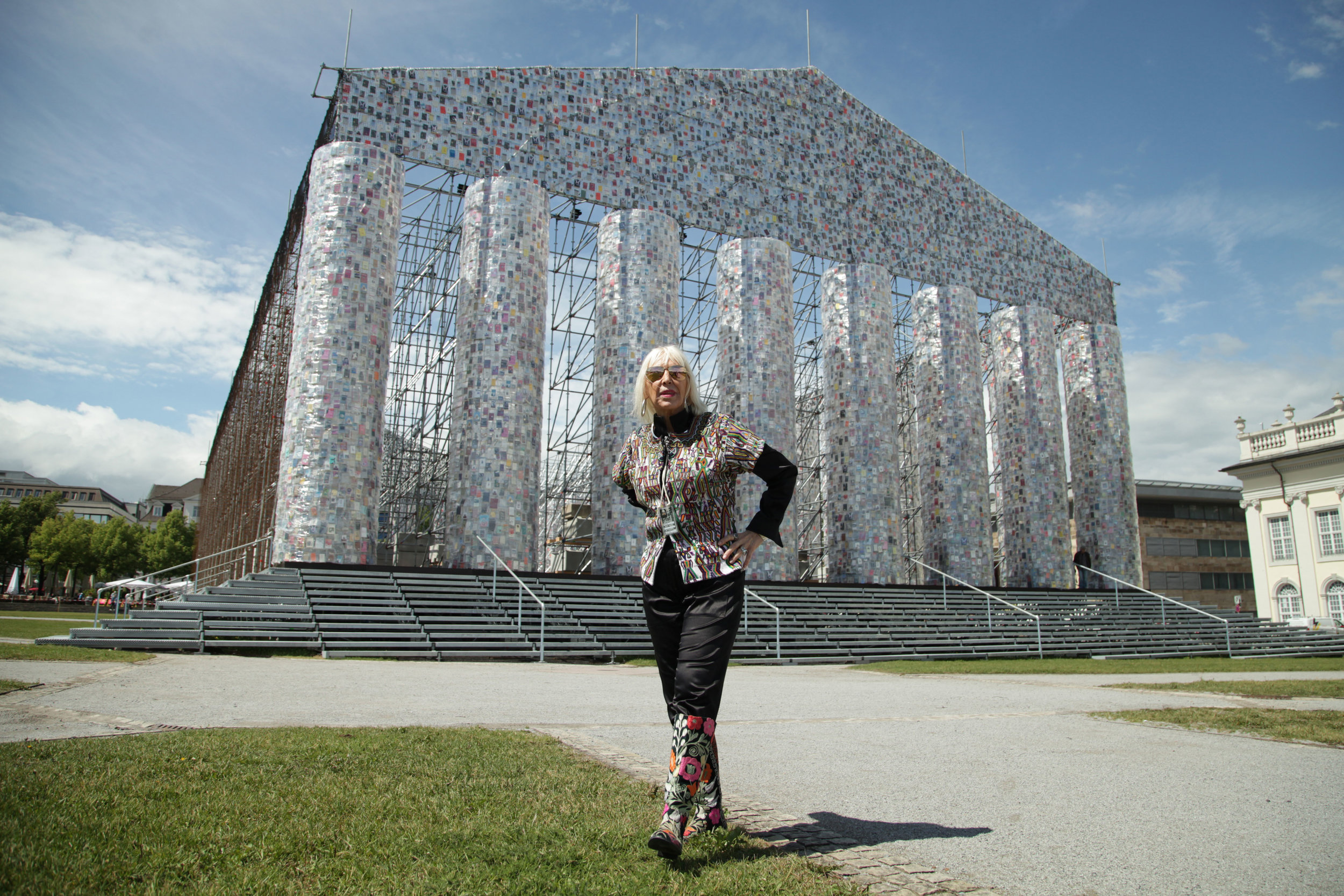 """Marta Minujín poses in front of """"The Parthenon of Books"""""""