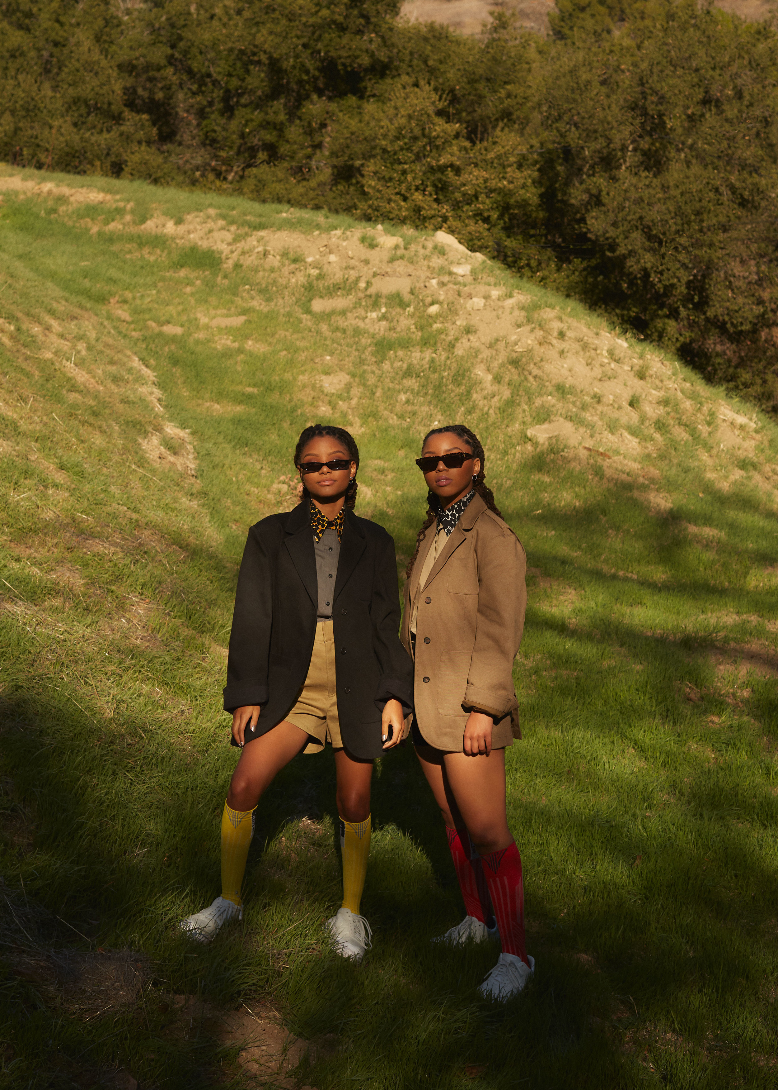 Chloe x Halle  | Photos by Robin Harper | Fashion Credits - Left to right: PRADA jacket, shirt, shorts, and socks, NIKE 1 REIMAGINED jester sneakers, ROBERI & FRAUD sunglasses, and GABRIELA ARTIGAS earrings. PRADA jacket, shirt, shorts, and socks, NIKE 1 REIMAGINED Jester sneakers, CUTLER & GROSS sunglasses, and GABRIELA ARTIGAS earrings