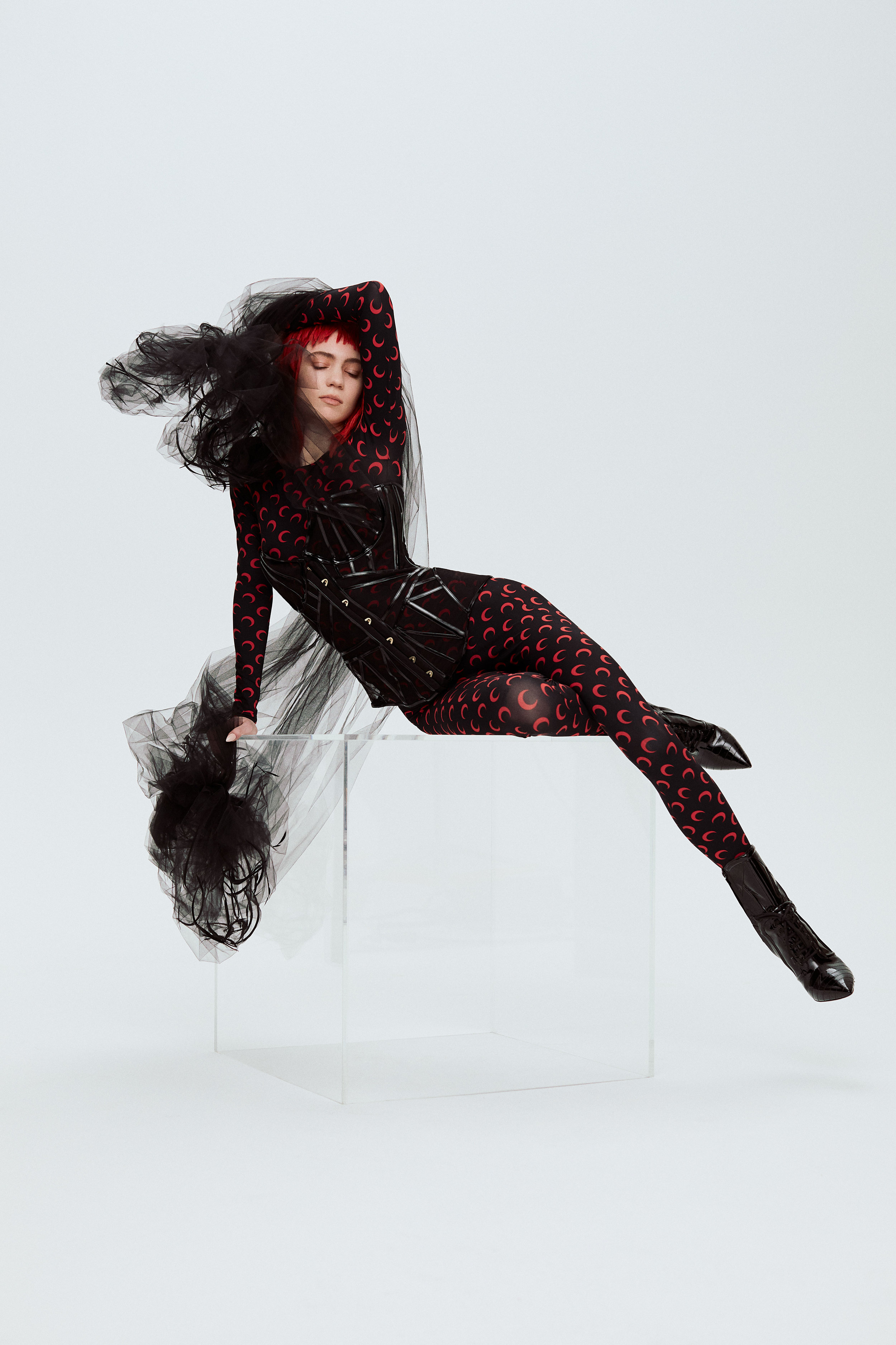ALIONA KONONOVA     cape,   MARINE SERRE     bodysuit,   AGENT PROVOCATEUR     bustier, and   MOSCHINO     boots.