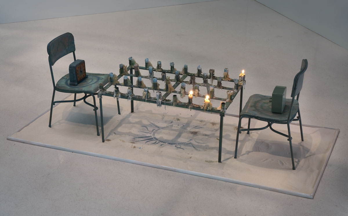 """The Game of Time,"" (2013). Tableau: Child's chair with orange face clock, Metal table with candles, Rectangular clock face in sand, and Child's chair with green clock. 68 x 30 x 20 inches. Courtesy the Artist and Roberts & Tilton, Culver City. Photo: Robert Wedemeyer."
