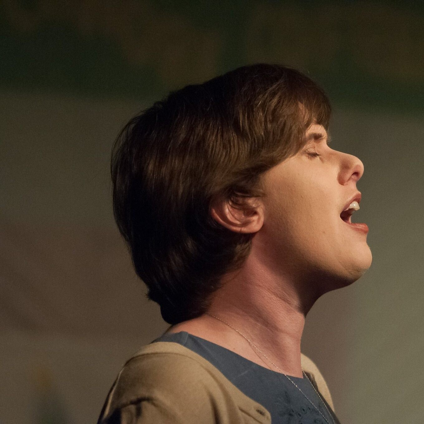Image Description: Emily Rose Cole with short hair, eyes closed, singing.