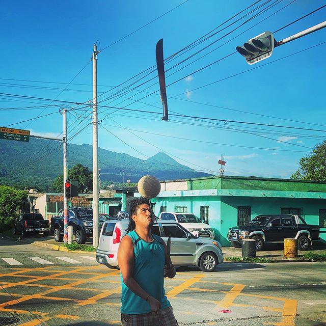 At the stoplight / Machete juggling, ball in the air, the San Salvador watching over his shoulder . . .  #EverydayLatinAmerica #natgeolatam #ourstreets #streetphotography #streetphotographymagazine #lensculturestreets #streetphotographycommunity #lensculture #everybodystreet #everydayeverywhere #iglatinoamerica #ig_street #storyofthestreets #streetlife_awards #outofthephone #streetphotographyinternational #SPicollective #streets_storytelling #thestreetphotographyhub #santatecla #elsalvador #machete #juggling