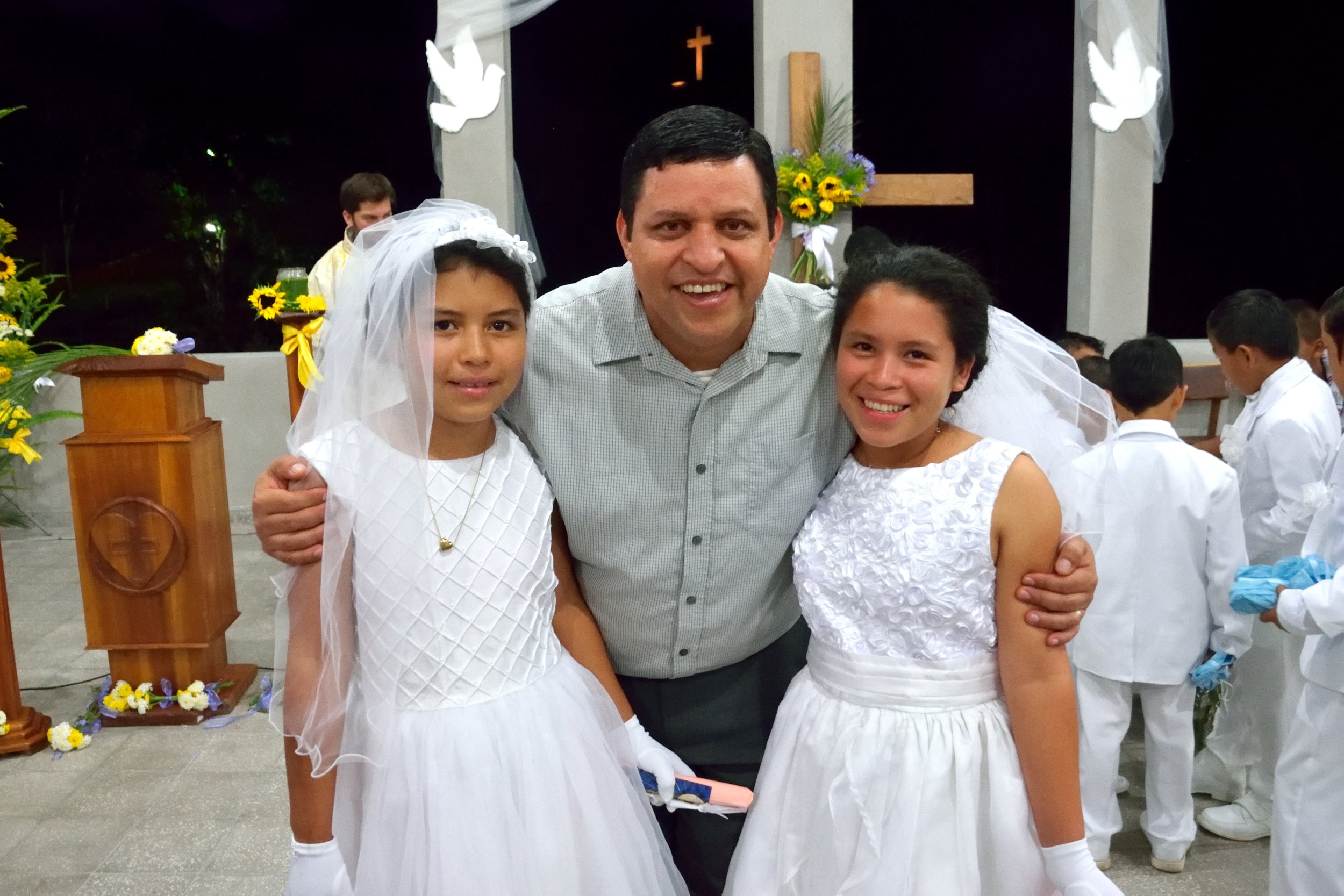 Virginia and one of her sisters with Padrino Wilson after they received their First Communion last April.