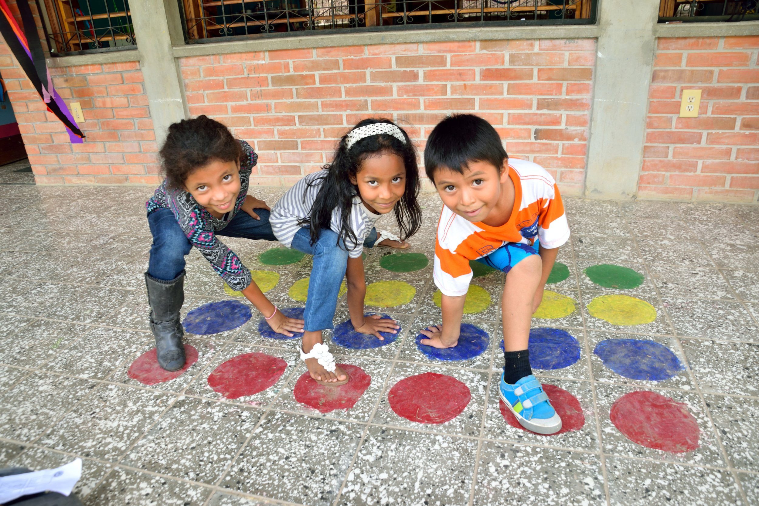 Soledad, pictured on the left, with two friends playing Twister at Día del Niño (Children's Day) this past September.